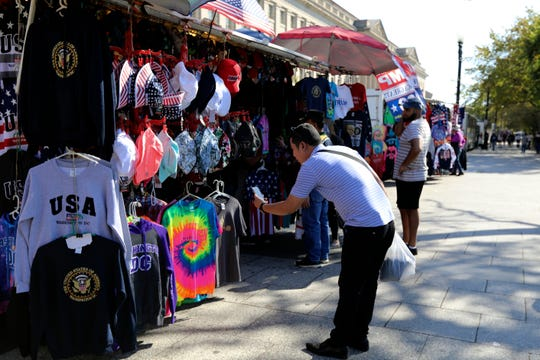 A Chinese tourist takes pictures of Washington, D.C., T-shirts at a tourism kiosk.