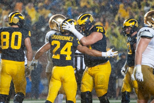 Michigan offensive lineman Jon Runyan celebrates with running back Zach Charbonnet after Charbonnet ran for a touchdown in the second quarter against Notre Dame.