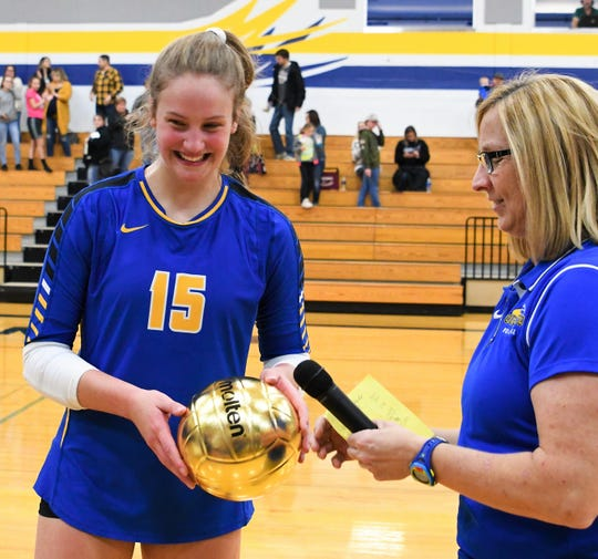 Oconto's Cora Behnke reached 1,000th career kills in the regional semi-final match against Crandon on Thursday night.  Coach Nancee Bucheger,  right, presented her with the golden volleyball to mark the accomplishment.