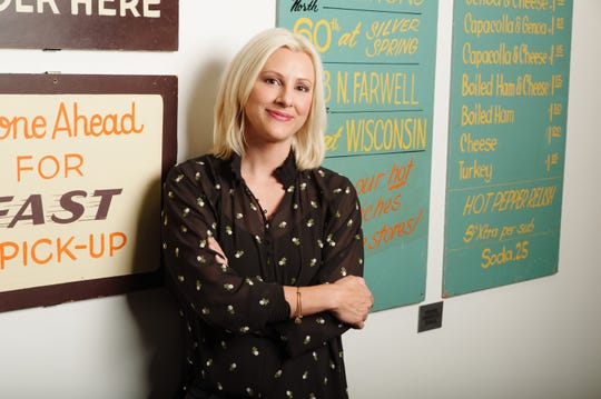 Cousins Subs CEO Christine Specht stands in front of signs at the Menomonee Falls headquarters. The signs were used at Cousins Subs shops started by her father and his cousin in 1972.