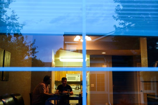 Michael Haring and his son, Anthony, talk while eating dinner together in their townhouse in Longmont, Colorado.