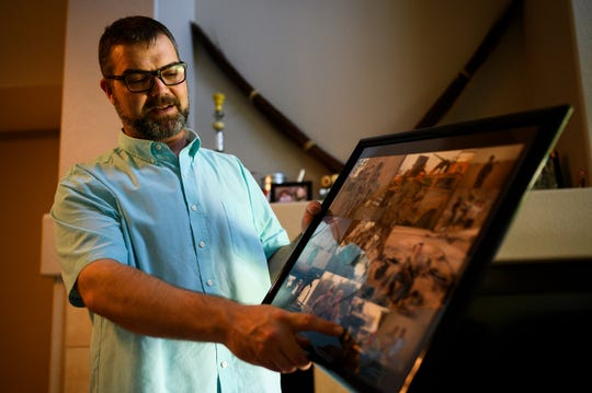 Michael Haring, an Army veteran, shows photographs of when he served in Iraq inside his townhouse in Longmont, Colorado.