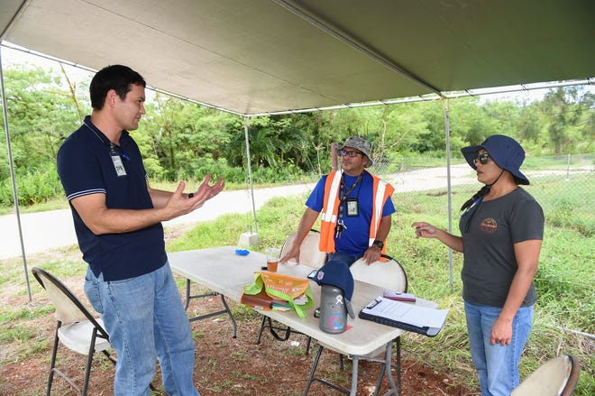 CHamoru Land Trust Administrative Director Jack Hattig III, left, meets with CLTC engineering technician Melvin O. Javier and land agent Tina Tainatongo on Swamp Road in Dededo in this Oct. 28, 2019, file photo.