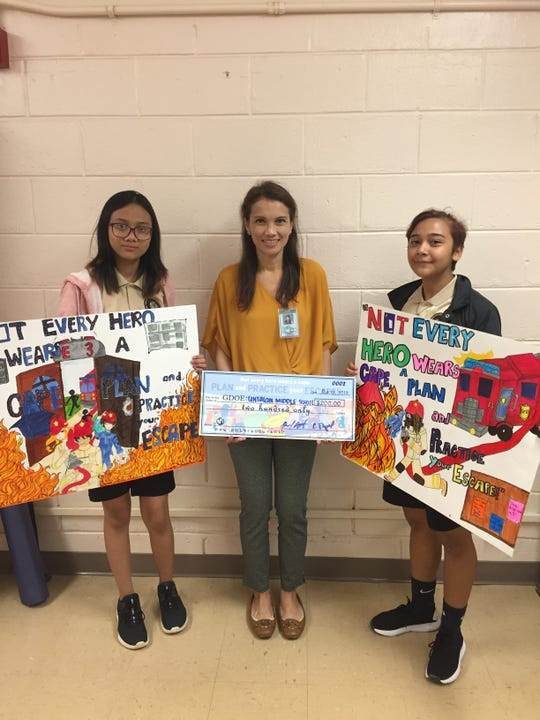 """From left: Jhaz Gomez 8th grade, Agnes Guerrero principal and Jayanna Sablan 8th grade are the winners of the Guam Fire Department's Middle School Poster contest held Oct. 12 Micronesian Mall. This year's theme was """"Not every hero wears a cape: Plan and practice your escape."""""""