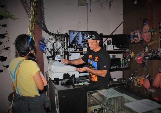 Dungeon owner Jeff Moylan handles the store cash register.