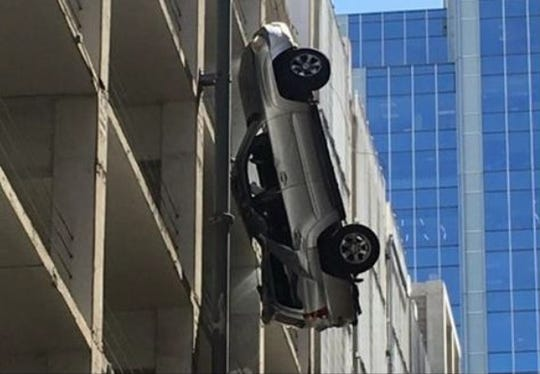 """This photo, submitted as part of a lawsuit against the owners of a parking garage in Austin, shows a vehicle suspended by the parking garage's cable barrier in September 2016. """"The driver was (miraculously) able to climb out of the sunroof and make his way safely back into the garage,"""" the Austin Fire Department posted on Facebook."""