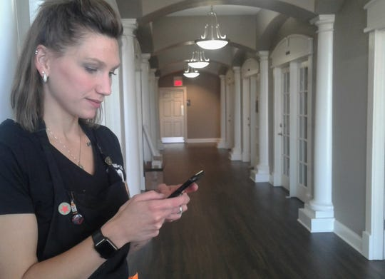 Molly Koch checks her phone between clients in the hallway of 965 Solon & Spa in North Liberty. She's one of several area hair stylists who donate their services to Shelter House clients and to other organizations.
