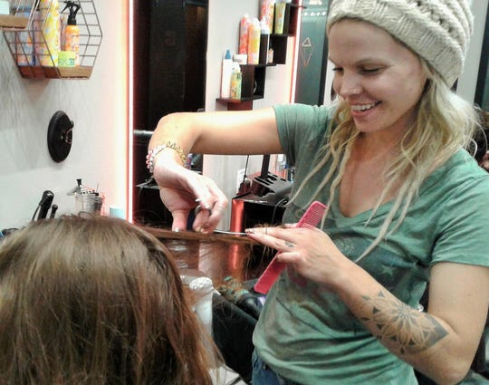 Lindsay Parker, shown here working at Salon Ludic in North Liberty, says she enjoys donating her stylist services for Shelter House in Iowa City. She also gave free haircuts to kids heading back to school during a fall program sponsored by Life Church in Coralville.