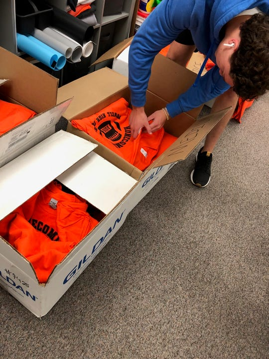 Caden Carr separates some orange Homecoming shirts destined for freshmen.