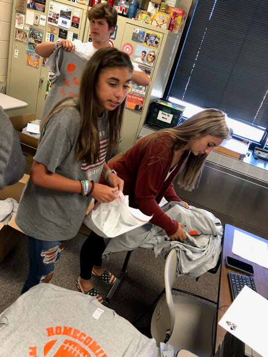 Jordan Blair, left, and Sydney Chianelli, students in Jennifer Morgan's Retail Operations class, get Homecoming shirts ready for distribution.