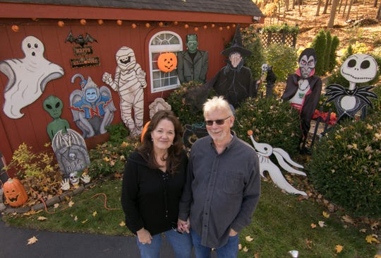 Leanne and Gene Szatkowski stand in front of the hand-painted and cutout figures Leanne has produced for Halloween at their Parshallville Road home Monday, Oct. 28, 2019.
