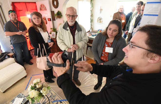 James Frangella of Ground Level Solutions shows how an infrared camera shows how well the insulation is working inside the home at 541 Cline Ave. during an open house on Monday morning.