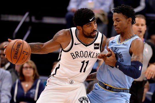 Brooklyn Nets guard Kyrie Irving (11) handles the ball against Memphis Grizzlies guard Ja Morant in the first half of an NBA basketball game Sunday, Oct. 27, 2019, in Memphis, Tenn. (AP Photo/Brandon Dill)