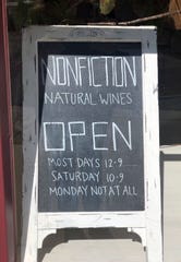 A sign outside Nonfiction Wines advertises its hours.