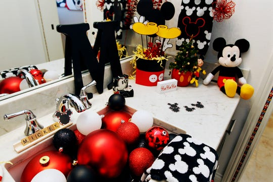 Colorful ornaments and other Mickey Mouse knickknacks take over the bathroom sink and counter.