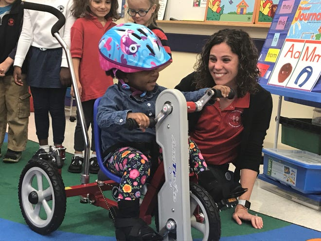 Zora Bastoky tries out her new bike with help from Music City Trykes president Ashley Schilling at Primrose School of Murfreesboro on Friday, Oct. 25, 2019.