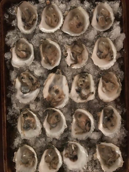 Pemaquid oysters, shucked and on a bed of crushed ice in a sheet pan.