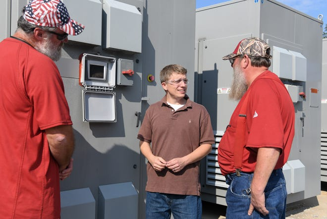"""Electricians Lon Britt, left, and Robert Campbell, right, along with electrical engineer Adam Webb look at a rectifier, like one that was responsible for an un-commanded """"runaway"""" condition, outside the AEDC Aerodynamic and Propulsion Test Unit at Arnold Air Force base, Sept. 27, 2019. Webb improved the logic used in the Programmable Logic Controllers on the units to handle un-commanded """"runaways"""" and allowed him to identify the part at fault. (This image has been altered by obscuring items for security reasons.)"""