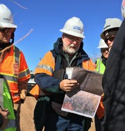 At center, Mark Hutson examines an aerial map of the San Juan Generating Station and surrounding area, Monday, Oct. 28, 2019, while standing near the Shumway Arroyo in Waterflow.