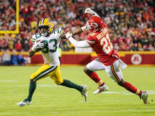 Oct 27, 2019; Kansas City, MO, USA; Green Bay Packers running back Aaron Jones (33) runs against Kansas City Chiefs defensive back Bashaud Breeland (21) during the second half at Arrowhead Stadium.