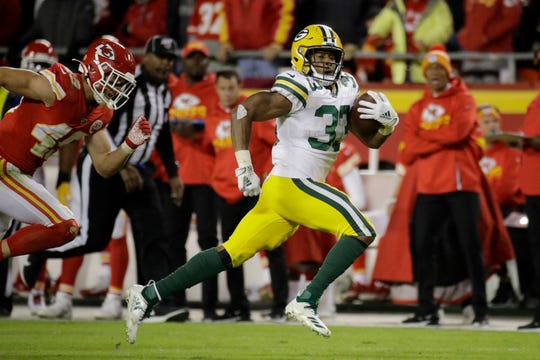Green Bay Packers running back Aaron Jones (33) takes a pass for a long touchdown in front of Kansas City Chiefs safety Daniel Sorensen, left, during the second half of an NFL football game in Kansas City, Mo., Sunday, Oct. 27, 2019.