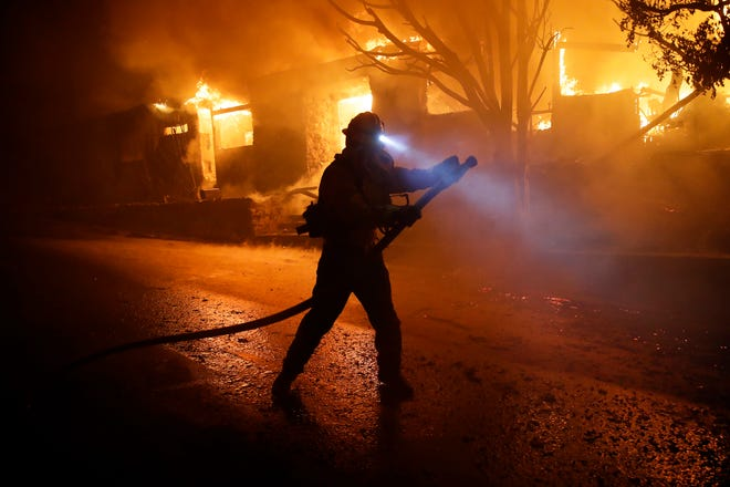 A firefighter gets in position to hose down flames as a home burns in the Getty fire area along Tigertail Road Monday, Oct. 28, 2019, in Los Angeles.