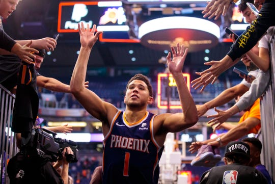 Phoenix Suns guard Devin Booker celebrates with fans as he leaves the court after defeating the Los Angeles Clippers at Talking Stick Resort Arena.