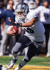 Nevada Wolf Pack quarterback Cristian Solano (13) runs against the Wyoming Cowboys during the first quarter at Jonah Field War Memorial Stadium.