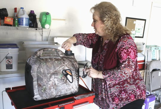 Anderson Vice Mayor Melissa Hunt fires up a generator to keep a friend's refrigerator-freezer running on Monday, Oct. 28, 2019, during the PG&E power outage. Hunt was house-sitting and taking care of her friend's three dogs.