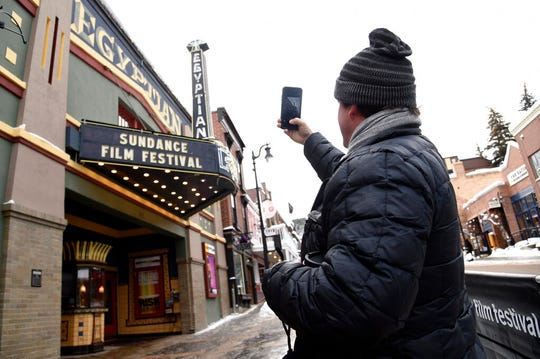 """FILE - In this Jan. 24, 2019, file photo, Matt Arnett of Atlanta, Ga, producer of the Sundance Film Festival narrative short """"I Snuck Off the Slave Ship,"""" takes a picture of the Egyptian Theatre marquee on the first day of the 2019 Sundance Film Festival, in Park City, Utah. The money spent by TV and film production crews in Utah has more than doubled over the last five years as directors are drawn to the state's proximity to Los Angeles and sweeping landscapes of red bluffs, deserts and lakes, according to a state report. (Photo by Chris Pizzello/Invision/AP, File)"""