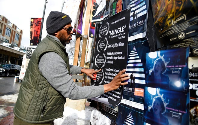 "FILE - In this Jan. 25, 2019, file photo, Ty Cooper, director of the narrative short ""Mingle,"" puts up a poster on Main Street to promote his film during the second day of the 2019 Sundance Film Festival, in Park City, Utah.  The money spent by TV and film production crews in Utah has more than doubled over the last five years as directors are drawn to the state's proximity to Los Angeles and sweeping landscapes of red bluffs, deserts and lakes, according to a state report.  (Photo by Chris Pizzello/Invision/AP, File)"