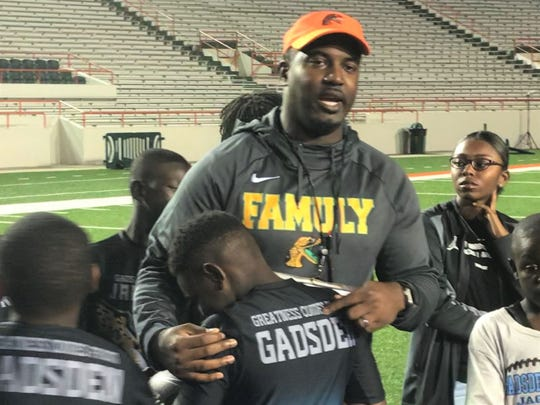 FAMU head coach Willie Simmons addresses his players after practice Sunday evening about being role models with members of the Gadsden County Jaguars in the huddle.