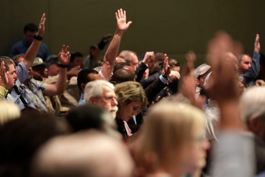 Audience members raise their hands during the City Commission ethics workshop to show they attended to support for City Manager Reese Goad.