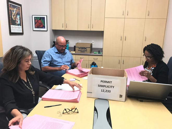 Oxnard City Clerk Michelle Ascencion, right, and other staff members are seen in this 2019 file photo counting the signatures in support of five proposed ballot measures written by Aaron Starr.