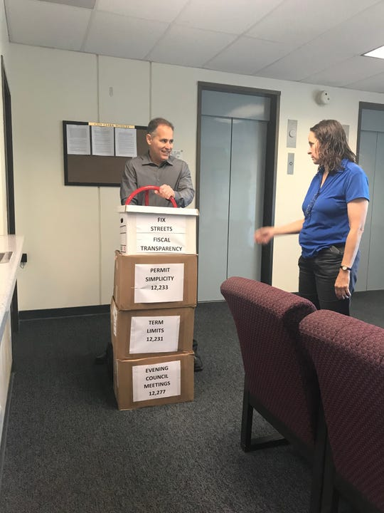 Aaron Starr, left, and Alicia Percell submit boxes of signed petitions on Monday supporting their ballot initiatives regarding Oxnard government.