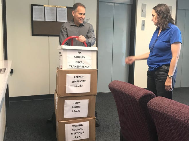 Aaron Starr, left, and Alicia Percell submit boxes of signed petitions in 2019 supporting their four ballot initiatives regarding Oxnard government. Among them is a measure on City Council term limits.