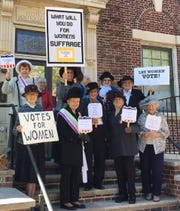 Members of the Daughters of the American Revolution and friends celebrate the right to vote with antique and vintage hats and placards with campaign quotes from early 1900s.