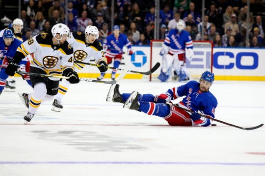 New York Rangers defenseman Brendan Smith (42) falls on the ice while skating against Boston Bruins defenseman Matt Grzelcyk (48) and center Par Lindholm (26) during the second period of an NHL hockey game, Sunday, Oct. 27, 2019, at Madison Square Garden in New York. (AP Photo/Mary Altaffer)