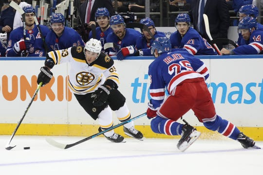 Boston Bruins center Brad Marchand (63) skates against New York Rangers defenseman Libor Hajek (25) during the first period of an NHL hockey game, Sunday, Oct. 27, 2019, at Madison Square Garden in New York. (AP Photo/Mary Altaffer)