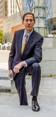 Attorney David Finger poses at the Beacon sculpture in Wilmington on Oct. 23, 2013.