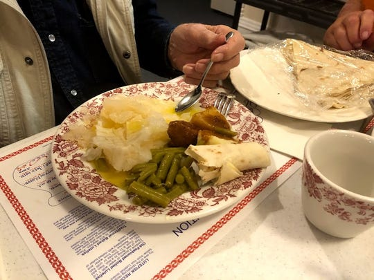 Author Jerry Apps prepares to dive into a traditional Norwegian dish of lutefisk, left, and  lefse.