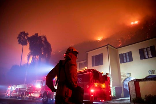 A firefighter watches a flames approach the Mandeville Canyon neighborhood during the Getty fire, Oct. 28, 2019, in Los Angeles.