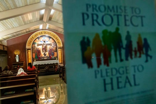A poster addressing sexual abuse within the Catholic church hangs as parishioners pray at a church in Guam.