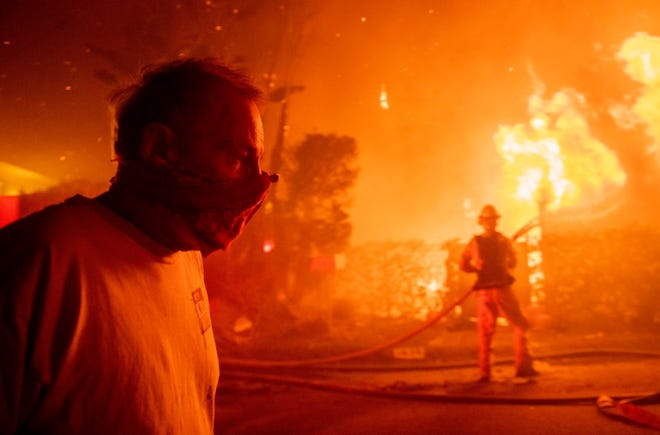 A man walks past a burning home during the Getty fire on Oct. 28, 2019, in Los Angeles.