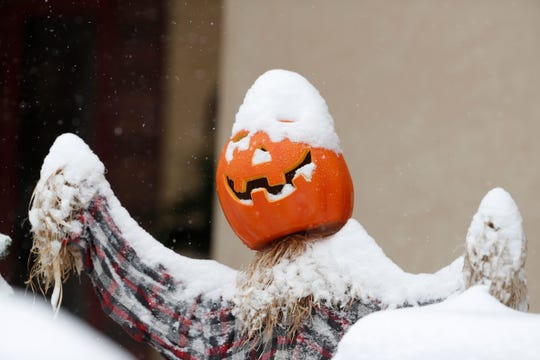 Snow covers a pumpkin used as part of a Halloween display outside a home as the season's first snow storm sweeps over the metropolitan area Thursday, Oct. 10, 2019, in Denver.