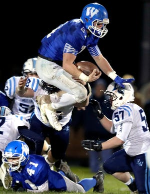Wrightstown High School's Ben Jaeger (21) leaps over Little Chute High School's Kyle VandeLeygraaf (57) during their WIAA Division 4 football playoff game Friday, October 25, 2019, in Wrightstown, Wis. Wrightstown defeated Little Chute 20-7.Wm. Glasheen/USA TODAY NETWORK-Wisconsin