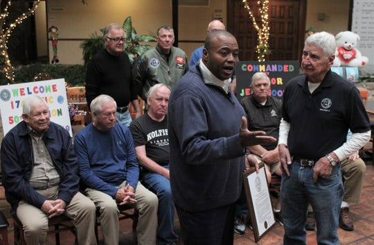 Mayor Anthony Williams, center, tells those gathered to honor Vietnam War veteran Jeff Goodin, right, who served for 22 years in the Army, that his proclamation may be the most significant of the more than 400 he has presented. Behind them are the nine members of the 174th Assault Helicopter Company who surprised Goodin with a 50-year reunion at MCM Elegante.