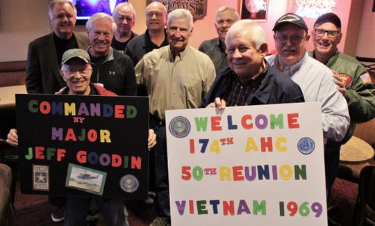 Nine men commanded by Maj. Jeff Goodin (center, in khaki shirt) in Vietnam in 1969 surprised him Monday with a 50th reunion. Coming from six states were, clockwise from left, Russ Lay (Pennsylvania, holding black sign), Bill Loken ( Nevada), Andy Anderson (Arizona), Tom Taggart (Montana), Bill Winans (Arizona), Robert Shoe (North Carolina), Al English (Nevada, green jacket), Jim Rich (North Carolina) and Mickey Burton (Louisiana, holding white sign).