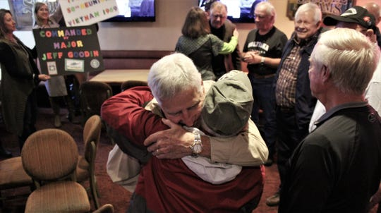 Jeff Goodin hugs Russ Lay (red Jacket) when Goodin was surprised Monday by nine men he commanded in 1969 as members of the 174th Assault Helicopter Company in Vietnam. Goodin then was a major, retiring as a lieutenant colonel.