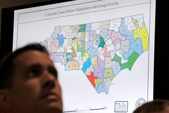 FILE - In this Monday, July 15, 2019 file photo, a state districts map is shown as a three-judge panel of the Wake County Superior Court presides over the trial of Common Cause, et al. v. Lewis, et al, in Raleigh, N.C. North Carolina judges on Monday, Oct. 28, 2019 blocked the state's congressional map from being used in the 2020 elections, ruling that voters had a strong likelihood of winning a lawsuit that argued Republicans unlawfully manipulated district lines for partisan gain. (AP Photo/Gerry Broome, File)